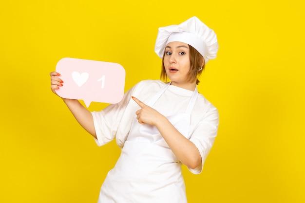Een vooraanzicht jonge vrouwelijke kok in wit kokkostuum en wit glb die roze teken op het geel houden