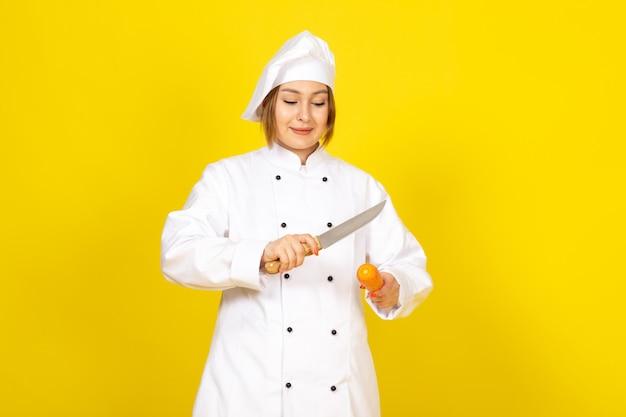 Een vooraanzicht jonge vrouwelijke kok in wit kokkostuum en wit glb-holdingsmes die scherpe carrott op het geel glimlachen