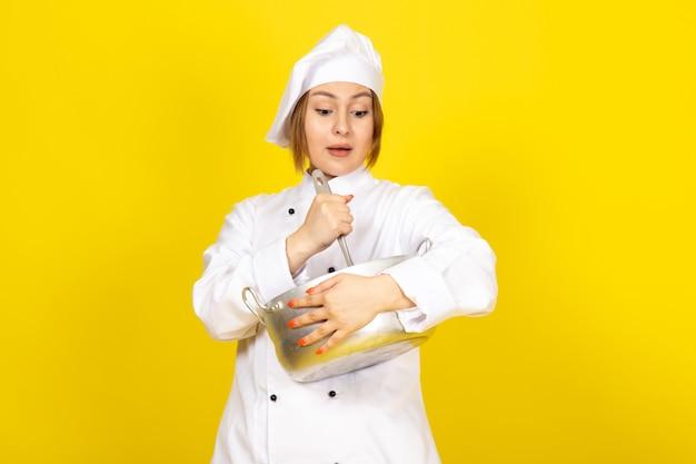 Een vooraanzicht jonge vrouwelijke kok in wit kokkostuum en witte glb die om zilveren pan houden die het mengen verrast op geel