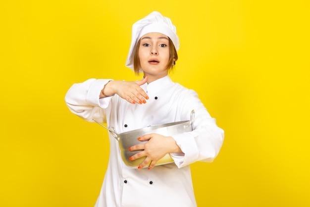 Een vooraanzicht jonge vrouwelijke kok in wit kokkostuum en witte glb die om zilveren pan houden die het op geel mengen