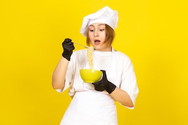 Een vooraanzicht jonge vrouwelijke kok in wit kokkostuum en witte glb in zwarte handschoenen die groene plaat houden die spaghetti op geel mengen
