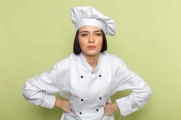 Een vooraanzicht jonge vrouwelijke kok in wit kokskostuum en pet die zich voordeed op de groene muur