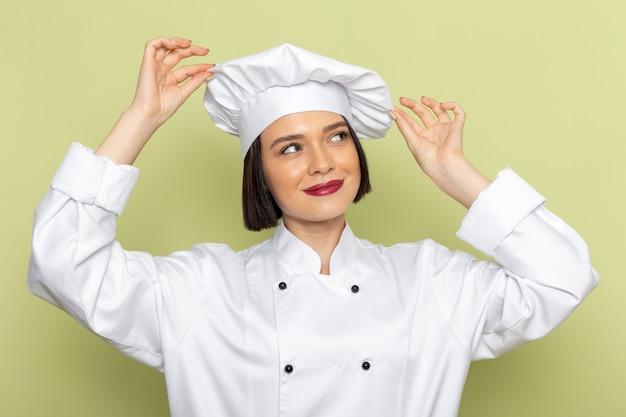 Een vooraanzicht jonge vrouwelijke kok in wit kokskostuum en pet poseren en dromen op de groene muur dame werk voedsel keuken kleur