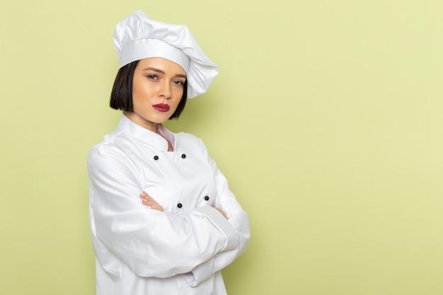 Een vooraanzicht jonge vrouwelijke kok in wit kokskostuum en pet poseren met ontevreden uitdrukking op de groene muur dame werken voedsel keuken kleur