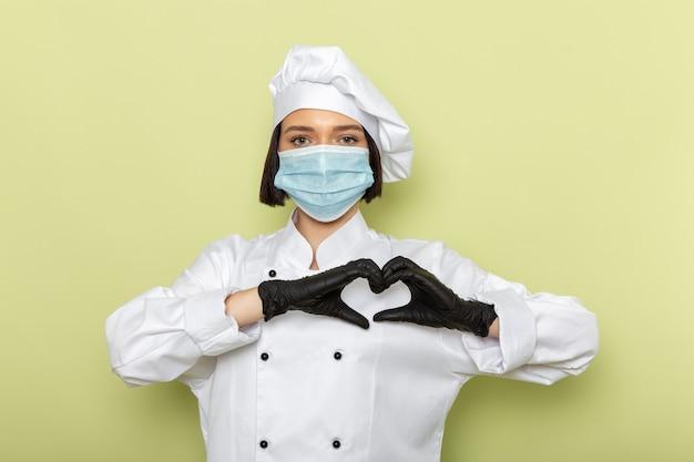 Een vooraanzicht jonge vrouwelijke kok in wit kookpak en pet met handschoenen en een steriel masker met een liefdesbordje op de groene muur.
