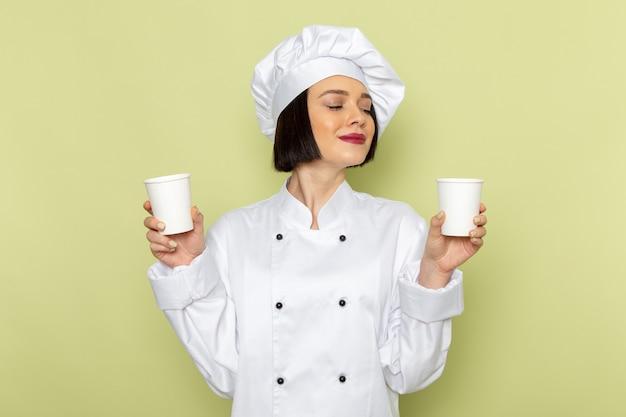 Een vooraanzicht jonge vrouwelijke kok in wit kookpak en pet met plastic bekers op de groene muur