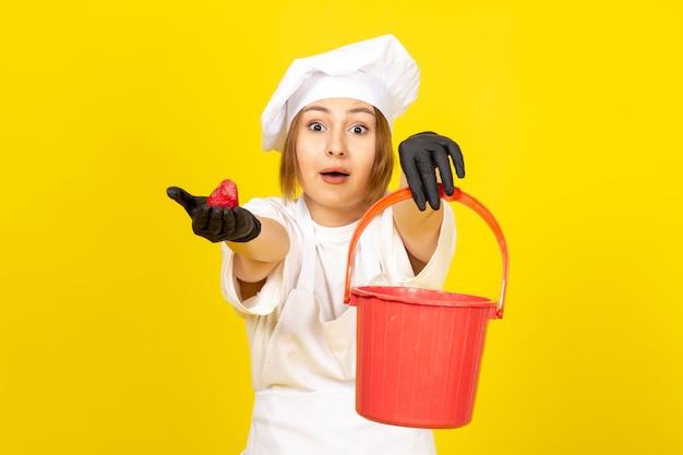 Een vooraanzicht jonge vrouwelijke kok in witte cook pak en witte dop in zwarte handschoenen met rode mand en aardbei op de gele