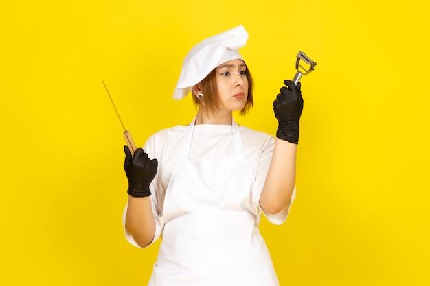 Een vooraanzicht jonge vrouwelijke kok in witte kok pak en witte dop in zwarte handschoenen met mes en plantaardige reiniger op de gele