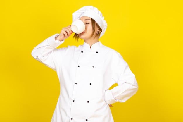 Een vooraanzicht jonge vrouwelijke kok in witte kok pak en witte dop koffie drinken op de gele