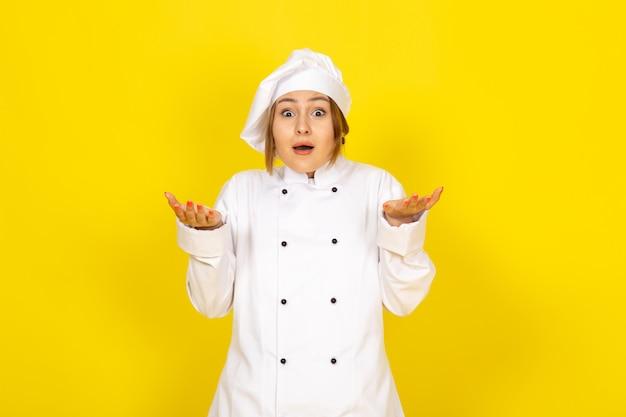 Een vooraanzicht jonge vrouwelijke kok in witte kok pak en witte dop opgewonden uitdrukking op de gele