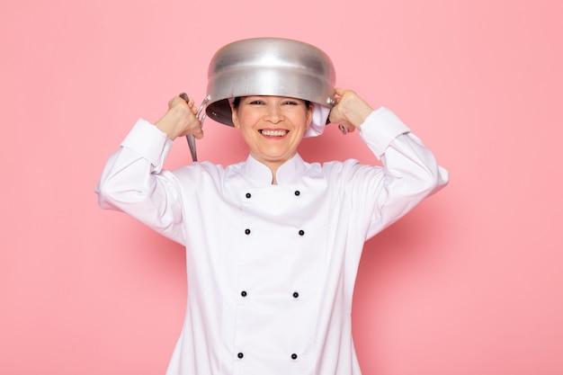 Een vooraanzicht jonge vrouwelijke kok in witte kok pak witte dop poseren met zilveren steelpan op haar hoofd lachen