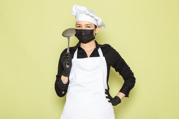 Een vooraanzicht jonge vrouwelijke kok in zwart shirt witte kok cape witte pet in zwarte handschoenen zwart masker poseren met grote zilveren lepel