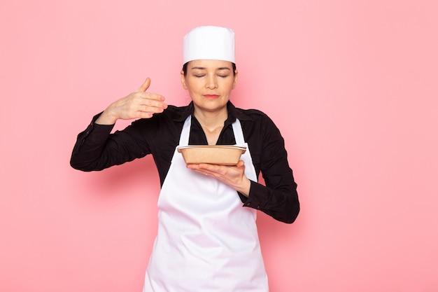 Een vooraanzicht jonge vrouwelijke kok in zwarte shirt witte kok cape witte dop poseren ruikende melk bruine kom