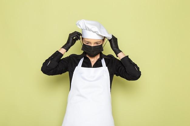 Een vooraanzicht jonge vrouwelijke kok in zwarte shirt witte kok cape witte pet poseren in zwarte handschoenen dragen zwarte masker poseren