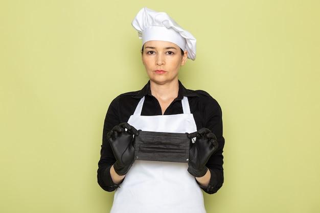 Een vooraanzicht jonge vrouwelijke kok in zwarte shirt witte kok cape witte pet poseren in zwarte handschoenen met zwarte masker poseren