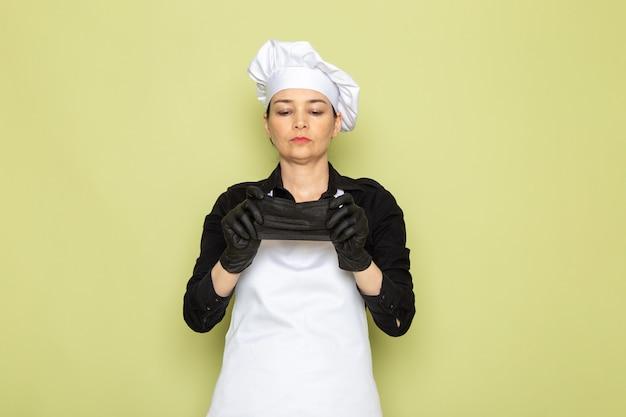 Een vooraanzicht jonge vrouwelijke kok in zwarte shirt witte kok cape witte pet poseren in zwarte handschoenen weanig zwart masker poseren