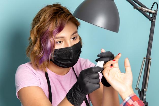 Een vooraanzicht jonge vrouwelijke manicure in roze t-shirt met zwarte handschoenen en zwart masker manicure op blauw