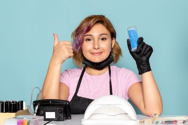 Een vooraanzicht jonge vrouwelijke manicure in roze t-shirt met zwarte handschoenen en zwart masker poseren en tonen als teken op blauw