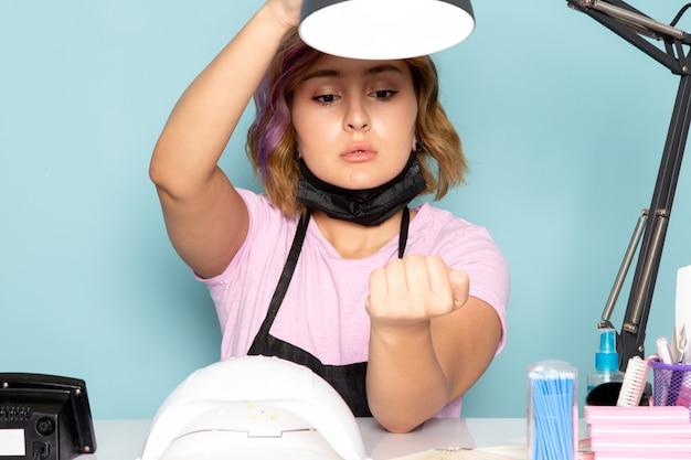 Een vooraanzicht jonge vrouwelijke manicure in roze t-shirt met zwarte handschoenen en zwart masker zit voor de tafel en controleert haar nagels op blauw
