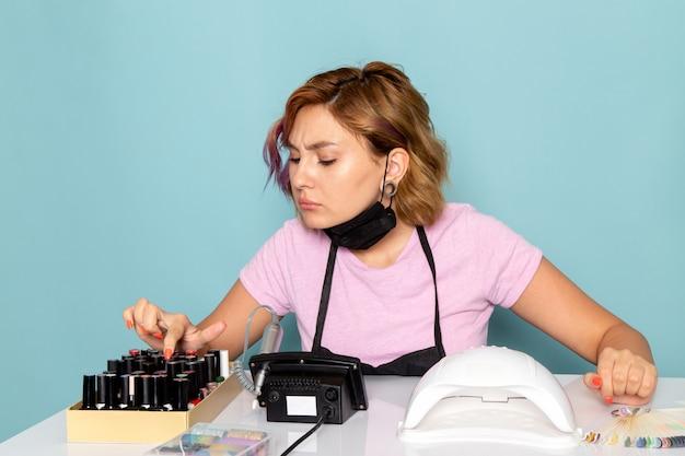 Een vooraanzicht jonge vrouwelijke manicure in roze t-shirt met zwarte handschoenen en zwart masker zit voor de tafel en controleert nagellakken op blauw