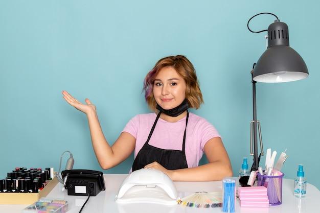 Een vooraanzicht jonge vrouwelijke manicure in roze t-shirt met zwarte handschoenen en zwart masker zit voor de tafel en lachend op blauw