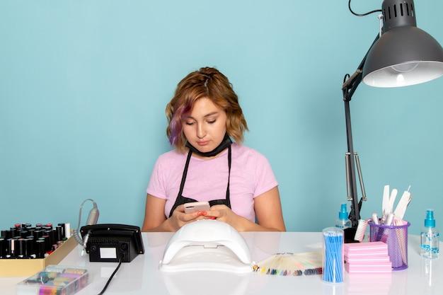 Een vooraanzicht jonge vrouwelijke manicure in roze t-shirt met zwarte handschoenen en zwart masker zit voor de tafel en met behulp van een telefoon op blauw