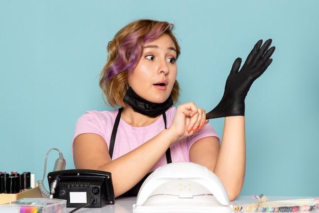 Een vooraanzicht jonge vrouwelijke manicure in roze t-shirt met zwarte handschoenen op blauw