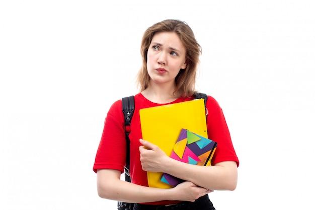 Een vooraanzicht jonge vrouwelijke student die in rode de holdingsvoorbeeldenboeken van de overhemds zwarte zak dossiers die op het wit denken