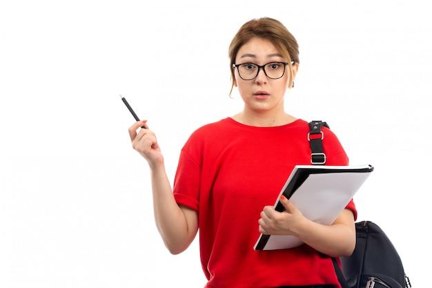 Een vooraanzicht jonge vrouwelijke student die in rode t-shirt zwarte jeans voorbeeldenboek op het wit houdt