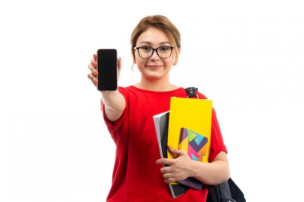 Een vooraanzicht jonge vrouwelijke student die in rode t-shirt zwarte jeans voorbeeldenboeken houdt glimlachend tonend smartphone op het wit