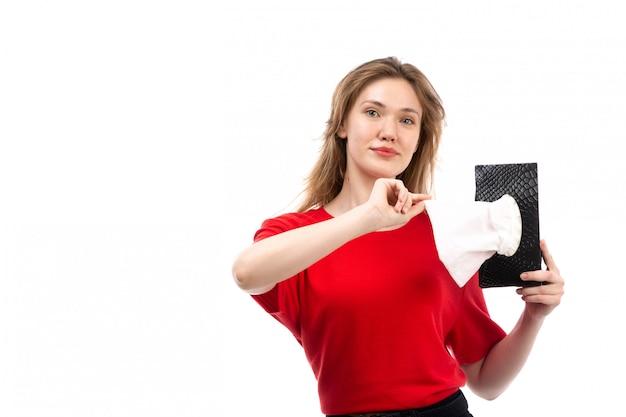 Een vooraanzicht jonge vrouwelijke student in de rode overhemd zwarte zak die nemend servet op het wit glimlachen
