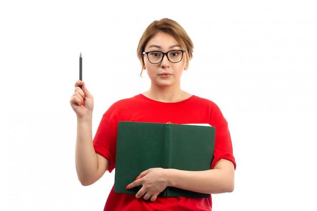 Een vooraanzicht jonge vrouwelijke student in het rode voorbeeldenboek die van de t-shirtholding nota's neerschrijven die idee op het wit denken