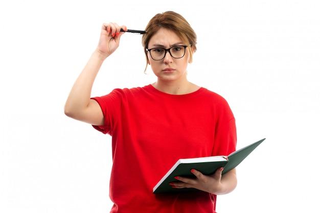 Een vooraanzicht jonge vrouwelijke student in het rode voorbeeldenboek die van de t-shirtholding nota's neerschrijven die op het wit denken