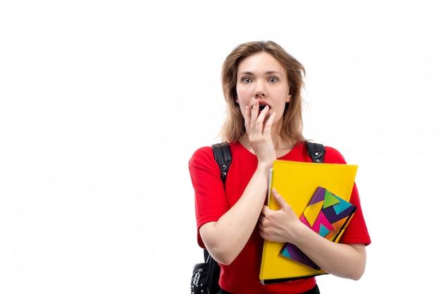 Een vooraanzicht jonge vrouwelijke student in rode de holdingsvoorbeelden van de overhemds zwarte zak geschokte uitdrukking op het wit