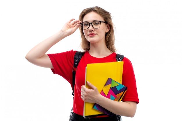 Een vooraanzicht jonge vrouwelijke student in rode de holdingsvoorbeeldenboeken van de overhemds zwarte zak dossiers die op het wit glimlachen