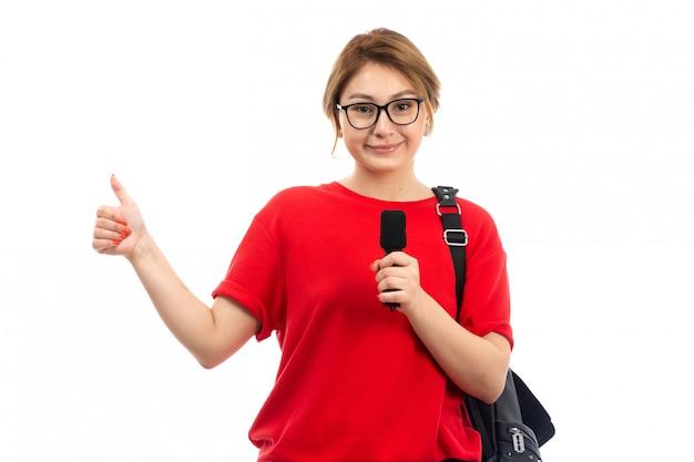 Een vooraanzicht jonge vrouwelijke student in rode t-shirt die de zwarte microfoon dragen die van de zakholding op het wit glimlachen
