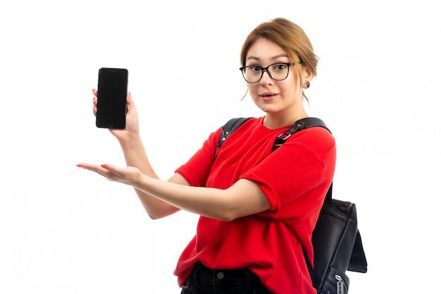 Een vooraanzicht jonge vrouwelijke student in rode t-shirt die zwarte zak draagt die zwarte smartphone houdt gebruikend op het wit