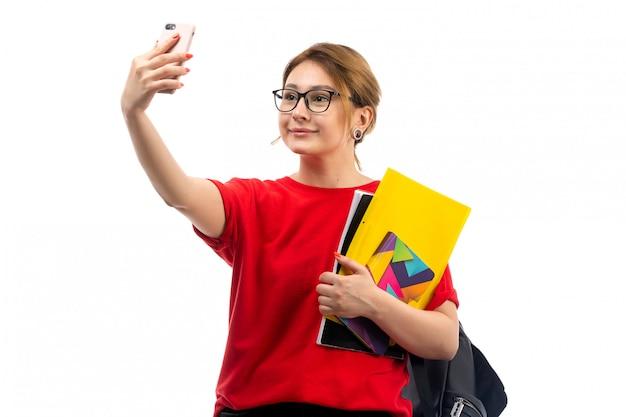 Een vooraanzicht jonge vrouwelijke student in rode t-shirt zwarte jeans die voorbeeldenboeken houden die een selfie op het wit nemen