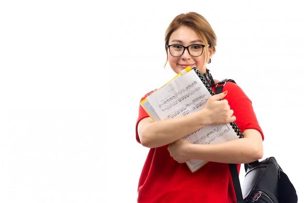 Een vooraanzicht jonge vrouwelijke student in rode t-shirt zwarte jeans die zwarte oortelefoons dragen die notaschrift houden glimlachend op het wit
