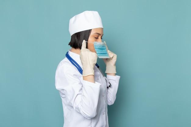 Een vooraanzicht jonge vrouwelijke verpleegster in wit medisch pak en blauwe stethoscoop draagt een masker op het blauwe bureau geneeskunde ziekenhuis arts