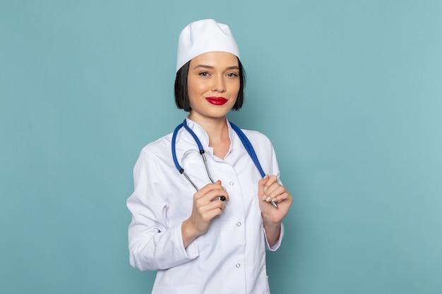 Een vooraanzicht jonge vrouwelijke verpleegster in wit medisch pak en blauwe stethoscoop lachend op de blauwe bureau geneeskunde ziekenhuis arts