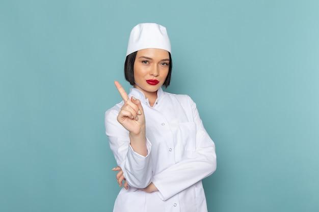 Een vooraanzicht jonge vrouwelijke verpleegster in wit medisch pak poseren op de blauwe bureau geneeskunde ziekenhuis arts