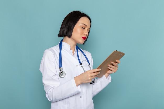 Een vooraanzicht jonge vrouwelijke verpleegster in witte medische pak blauwe stethoscoop bedrijf blocnote op de blauwe bureau geneeskunde ziekenhuis arts