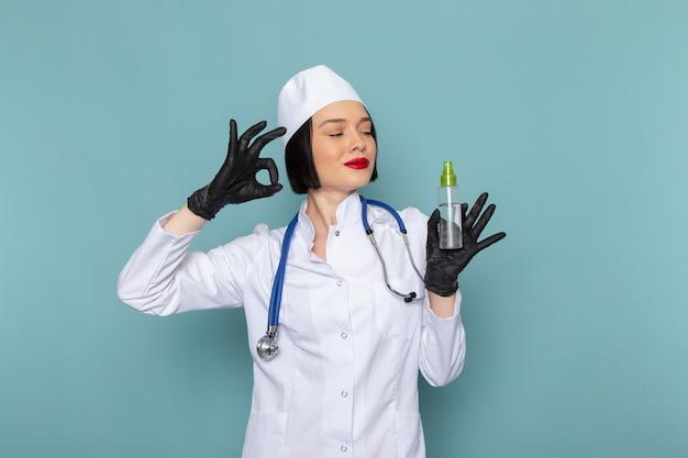 Een vooraanzicht jonge vrouwelijke verpleegster in witte medische pak en blauwe stethoscoop kolf te houden