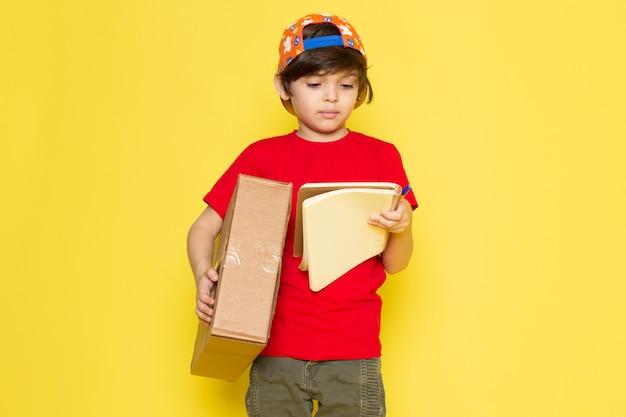 Een vooraanzicht jongetje in rode t-shirt kleurrijke pet en kaki broek met doos op de gele achtergrond