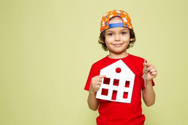 Een vooraanzicht jongetje in rood t-shirt met papieren huis op de steen gekleurde ruimte