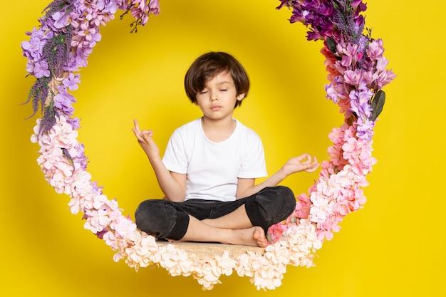 Een vooraanzicht jongetje in witte t-shirt zittend op de bloem gemaakt staan op het gele bureau