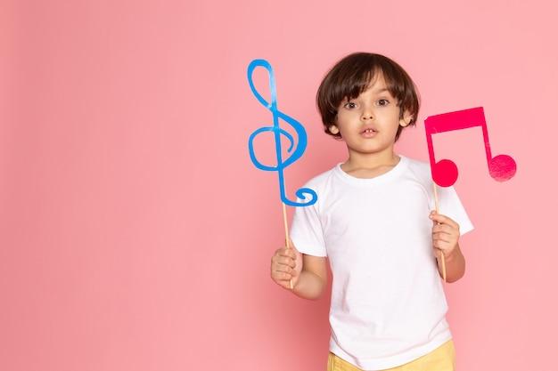 Een vooraanzicht jongetje met gekleurde borden in wit t-shirt op de roze ruimte