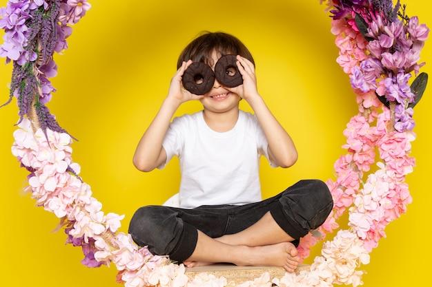 Een vooraanzicht kind jongen met paar choco donuts in wit t-shirt op het gele bureau