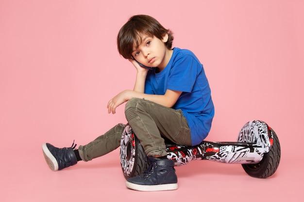 Een vooraanzicht klein kind in blauw t-shirt en kaki broek segway rijden op de roze ruimte